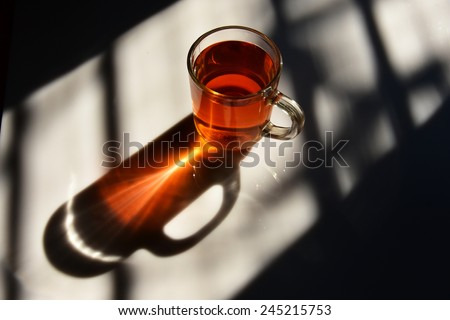 Good morning! Geometric patterns. Black tea in a glass mug shows sunlight refracted and converged. - stock photo