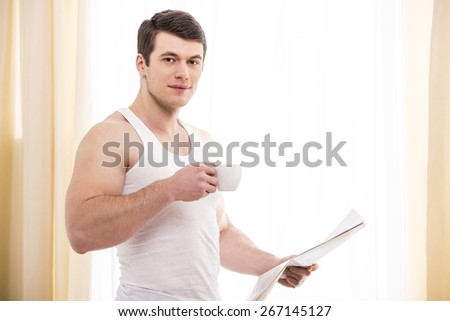 Good morning. Handsome young male  drinking coffee and reading a newspaper. - stock photo