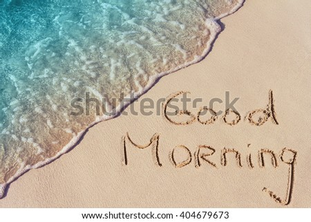 Good morning handwritten on a sandy beach with soft wave of blue ocean on background. - stock photo