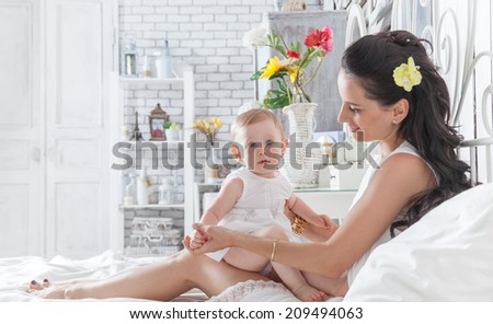 Good morning! Mother playing with a year-old daughter on the bed in the bedroom - stock photo
