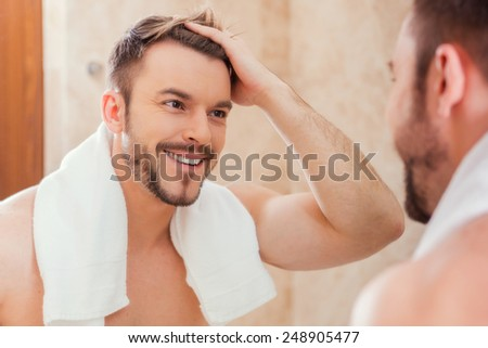 Good morning to me. Handsome young man touching his hair with hand and smiling while standing in front of the mirror - stock photo
