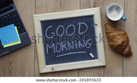Good morning written on a chalkboard next to a breakfast at the office - stock photo