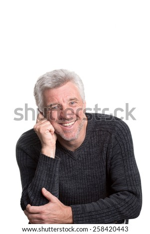 good-natured and bright mature older man sitting resting his head on his hand smiling - stock photo
