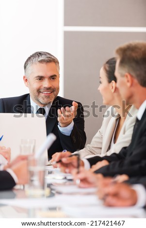 Good news for our company! Business people in formalwear discussing something while sitting together at the table - stock photo
