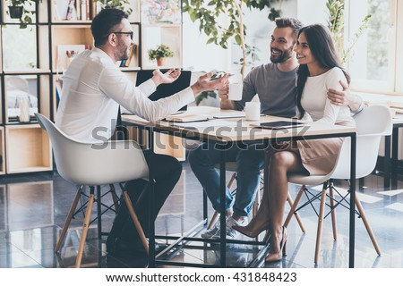 Good news for you! Cheerful young couple bonding to each other and listening to their financial advisor sitting at the desk in front of them  - stock photo