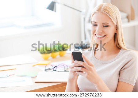 Good news from colleagues. Beautiful young woman holding mobile phone and smiling while sitting at her working place in office - stock photo
