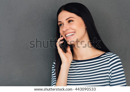 Good news from friend. Attractive young woman talking on the mobile phone and smiling while standing against grey background - stock photo