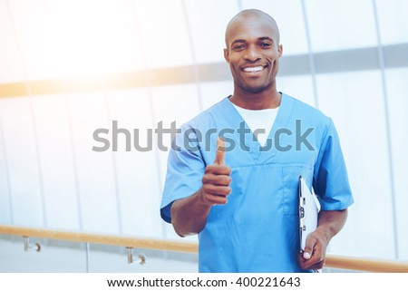 Good news! Happy young African doctor in blue uniform holding clipboard and showing his thumb up - stock photo
