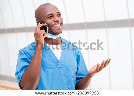 Good news! Happy young African doctor in blue uniform talking on the mobile phone and gesturing - stock photo