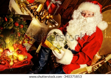Good old Santa Claus with Christmas gifts at his wooden house.  - stock photo