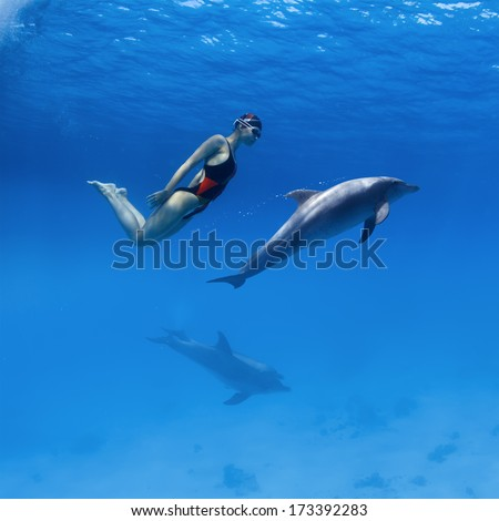 Good relationship with wild animals. Professional swimmer girl in sport swimsuit and friendly dolphins playing in deep blue sea underwater  - stock photo
