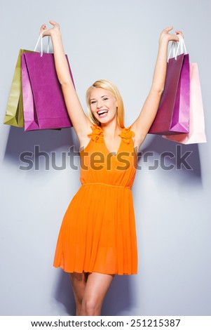 Good shopping. Beautiful young woman in pretty dress looking at camera and holding shopping bags standing against grey background   - stock photo