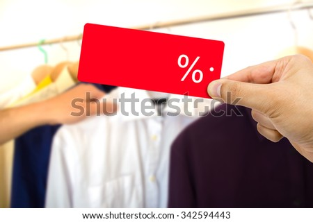 Good shopping sale concept.Man choosing clothes holding discount red label with percent sign in hand  - stock photo