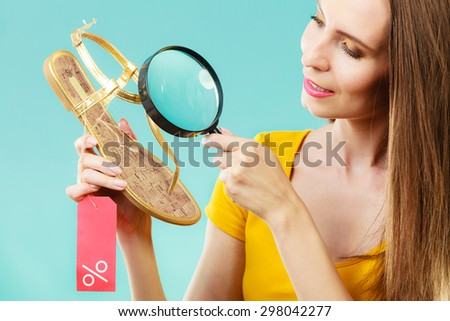 Good shopping summer sale concept. Fashionable woman choosing shoes searching through magnifying glass, discount red label with percent sign in hand - stock photo
