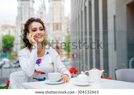 Good talk. Attractive young brunette woman talking on mobile phone while sitting in cafe outdoors. - stock photo