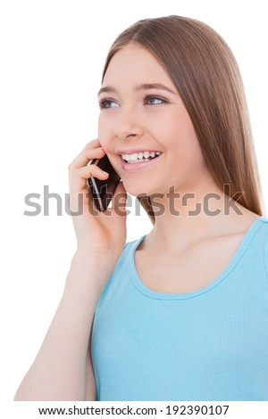 Good talk. Cheerful teenage girl talking on the mobile phone and smiling while standing isolated on white - stock photo