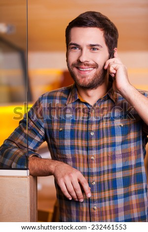 Good talk. Handsome young man talking on the mobile phone and smiling while standing indoors - stock photo