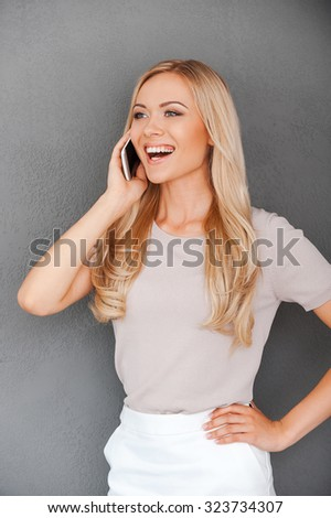 Good talk with friend. Attractive young blond hair woman talking on the mobile phone an smiling while standing against grey background - stock photo