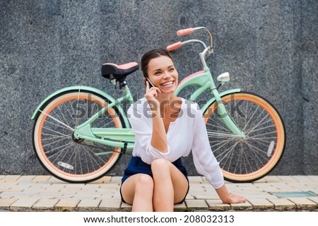 Good talk with friend. Attractive young smiling woman talking on the mobile phone while sitting at the roadside near her vintage bicycle  - stock photo
