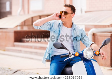 Good talk with friend. Cheerful young man sitting on scooter and talking on the mobile phone  - stock photo