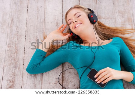 Good time with myself. Top view of beautiful young woman lying on the floor at her apartment listening to music through headphones - stock photo