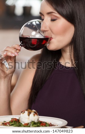 Good wine. Portrait of beautiful mature women drinking wine in restaurant - stock photo
