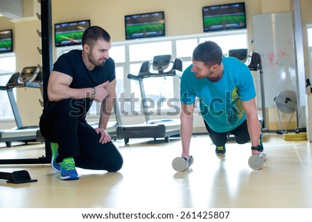 Good workout. Professional trainer and client in a fitness gym are having training - stock photo