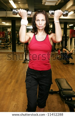 Goodlooking woman excercising in the gym. - stock photo
