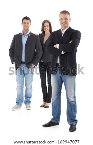 Goodlooking young casual businesspeople posing in studio, smiling, looking at camera, cutout, full length. - stock photo
