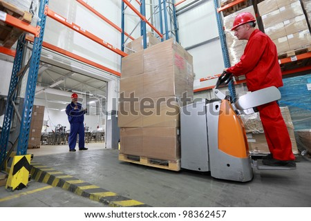 Goods delivery - two workers  with forklift loader working in storehouse - stock photo