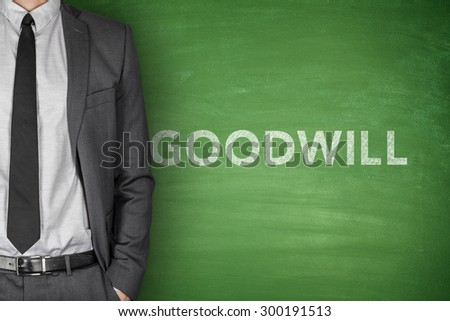 Goodwill text on green blackboard with businessman - stock photo