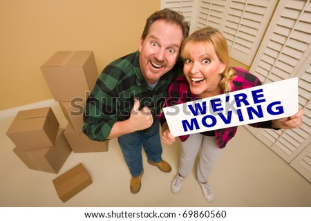 Goofy Thumbs Up Couple Holding We're Moving Sign in Room with Packed Cardboard Boxes. - stock photo