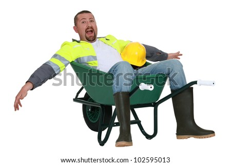 Goofy tradesman sitting in a wheelbarrow - stock photo