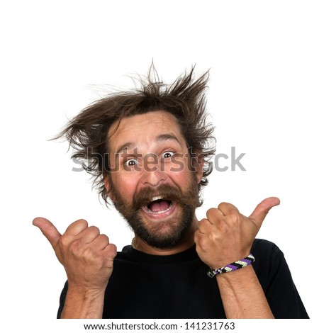Goofy young man grins at the camera while giving a thumbs up sign. Isolated on white background. - stock photo