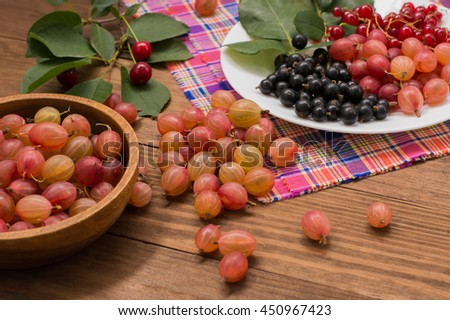 Gooseberries and currants on a wooden background. Close-up - stock photo