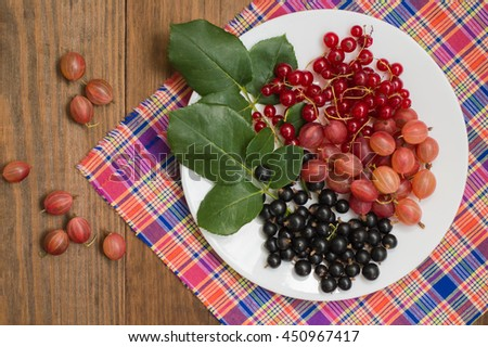 Gooseberries and currants on a wooden background. Top view. Close-up - stock photo