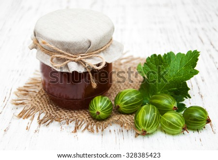 gooseberry jam with fresh berries on a wooden background - stock photo