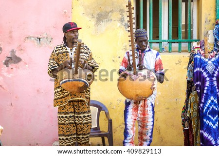 GOREE/SENEGAL - NOVEMBER 11, 2013: Two unidentified senegalese street musicians in traditional colorful clothes playing national musical instrument Kora at the street of Goree island, Dakar, Senegal - stock photo