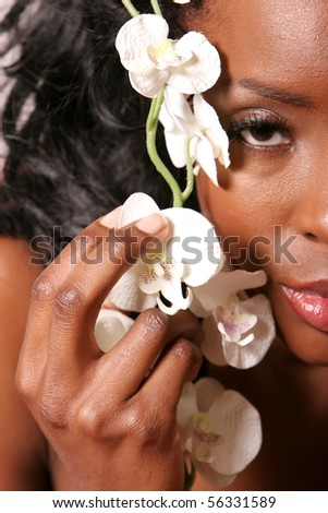 Gorgeous african american young woman holding white orchid flower on her face - stock photo