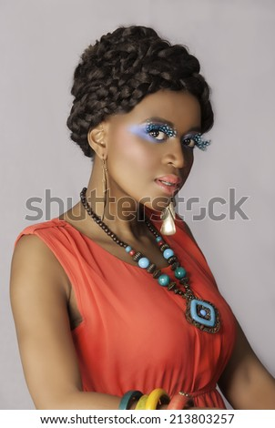 Gorgeous African woman with creative fantasy makeup in blue wearing a braided hairstyle, false lashes, necklace, orange dress and colorful bangles - stock photo