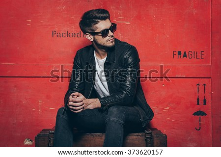 Gorgeous and stylish. Handsome young man in sunglasses keeping hands clasped and looking away while sitting on wooden chest against red background - stock photo