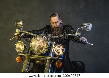Gorgeous Bearded Man in Black leather Jacket Riding on his Elegant Motorcycle and Looking at the Camera Against Smoky Background. - stock photo