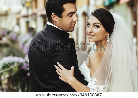 Gorgeous beautiful exotic brunette bride and handsome groom posing closeup - stock photo