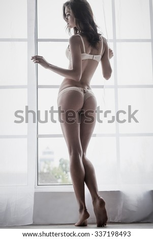 Gorgeous beauty. Full length rear view of beautiful young woman in lingerie standing near the window - stock photo