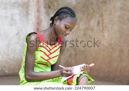 Gorgeous Black African Girl writing and drawing on her exercise book in a school using a pen. By buying this photo you help and support our social projects in Mali. Young schoolgirl education symbol. - stock photo