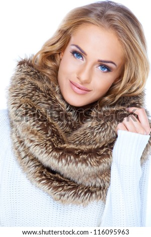 Gorgeous blond woman wearing winter fur scarf and smiling - stock photo