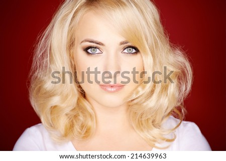 Gorgeous blond woman with shoulder length shiny healthy hair looking at the camera with a serious expression - stock photo