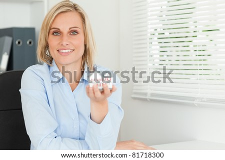 Gorgeous blonde businesswoman showing miniature house looking into the camera in her office - stock photo