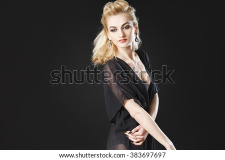 Gorgeous blonde girl smiling on black background playing with hair and wearing see through top - stock photo