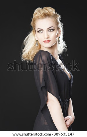 Gorgeous blonde girl smiling on black background playing with hair and wearing see through top and red lipstick  - stock photo